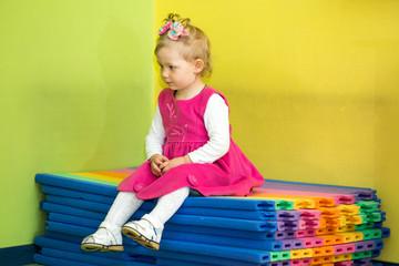 Little child girl playing in kindergarten in Montessori Class.
