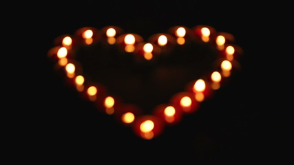 candles, grouped in heart shape on dark background