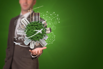 Businessman holding earth with buildings