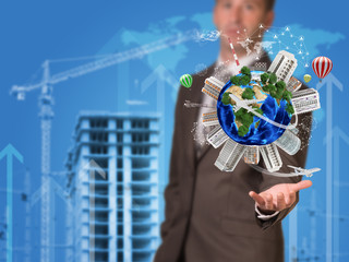 Businessman holding earth. Buildings as backdrop