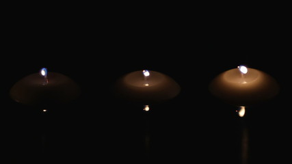 candles in a row on dark water surface