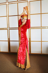 Pretty woman in red Andalusian costume poses