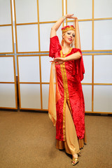Pretty woman in red Andalusian costume dances with shawls