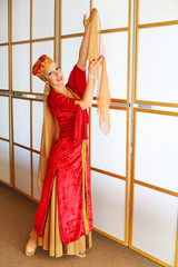 Pretty woman in red Andalusian costume poses with raised hands