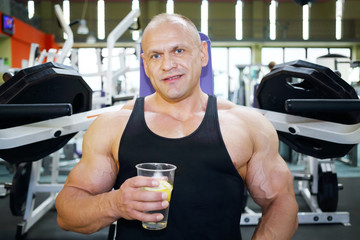 Bodybuilder in black jersey sits on exercise machine