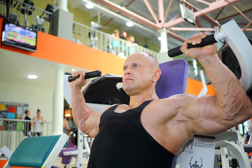 Bodybuilder in black jersey trains on exercise machine