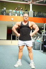 Bodybuilder in black jersey and white jogging shoes stands