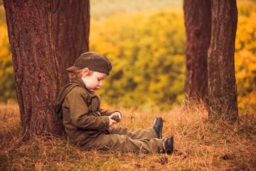 little boy under pine woods