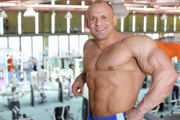 Happy shirtless sunburnt bodybuilder stands in big modern gym
