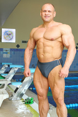 Happy sunburnt bodybuilder stands near indoor pool