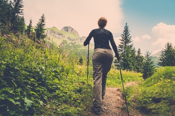 Woman with hiking poles walking in mountain landscape