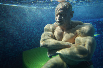 Bodybuilder with closed eyes in pool underwater
