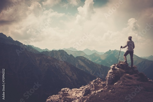 Woman hiker on a top of a mountain - 70996352