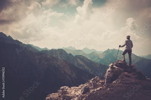 Leinwandbild Motiv Woman hiker on a top of a mountain