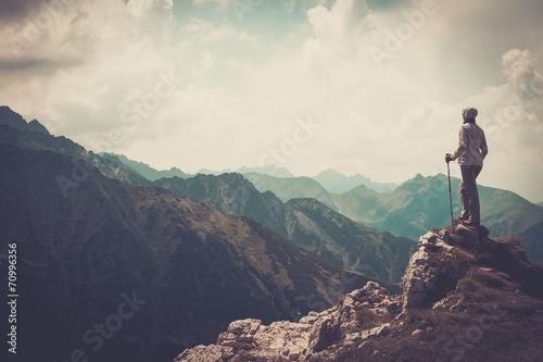 Leinwanddruck Bild Woman hiker on a top of a mountain