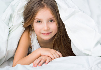 Beautiful little girl under a blanket