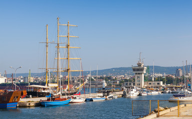 Big sailing ship and pleasure boats stand moored in Varna Port