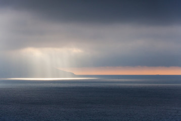 Bright sunlight goes through stormy clouds. Tangier bay, Morocco
