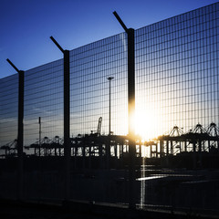 Port area fence with silhouettes of container cranes in the sunl