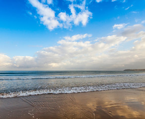 Atlantic ocean coast with waves and bright cloudy sky