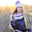 Portrait of beautiful smiling blonde woman in down jacket outdoo