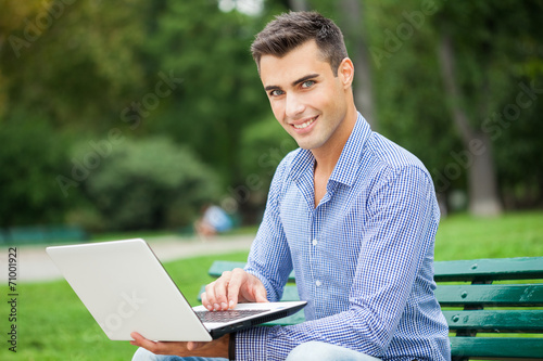 canvas print picture Young man using a laptop computer outdoors