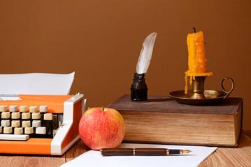 Typewriter, books and apple