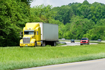 Yellow Semi Truck Leads Traffic On The Interstate