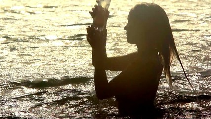 woman emerges from the sea and drinking water at sunset
