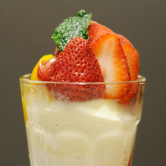 Strawberries yoghurt in glass gray background,