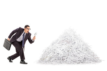 Businessman examining a pile of shredded paper
