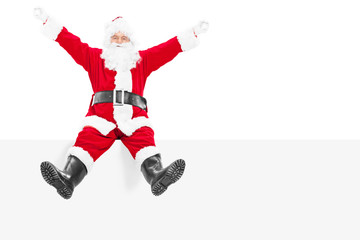 Delighted Santa Claus sitting on a blank panel