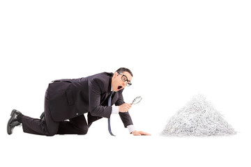 Businessman looking at a pile of shredded paper