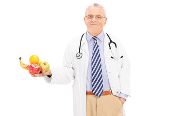 Mature doctor holding a bunch of fruits