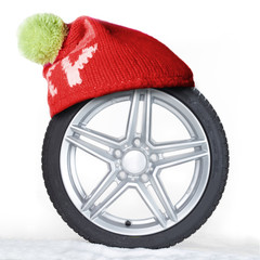 Winter tire with bobble hat in the snow