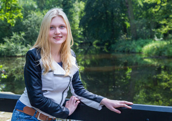 Blond girl leaning on fence near water in forest