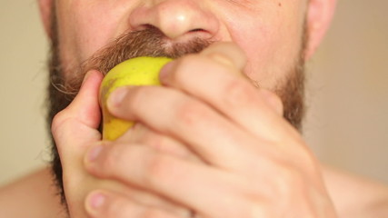 Bearded man eating apple