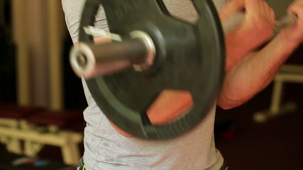 Young athletic man trains arms at the gym
