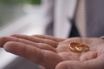 Wedding rings on the palm of the groom, marriage proposal