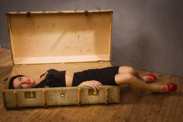 Pretty victim lying in the suit-case