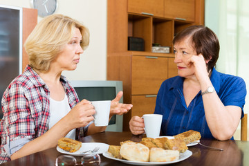 Two aged woman with cup of tea talking