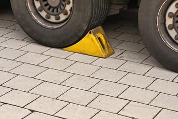 Ein gelber Bremsklotz - Unterlegkeil - vor einem Reifen