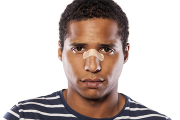 sad dark-skinned young man with adhesive tape over his nose