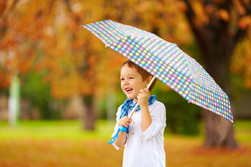 portrait of happy boy with umbrella under the rain