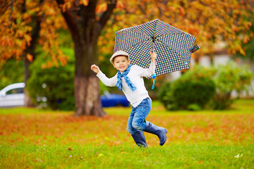 happy stylish boy with umbrella running in park