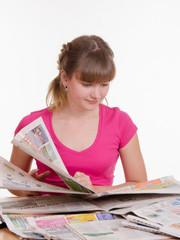 girl thumbs through the newspaper to find right ads