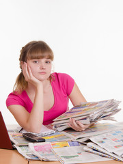 Girl sitting with a pile of newspapers at table