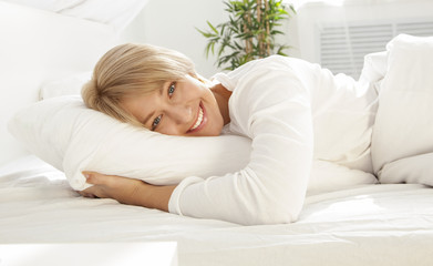 beautiful girl in a white bed in the morning, smiling