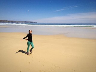 Young woman running in an empty beach in Scotland