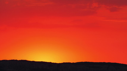 Bright red-orange sunrise behind the mountain